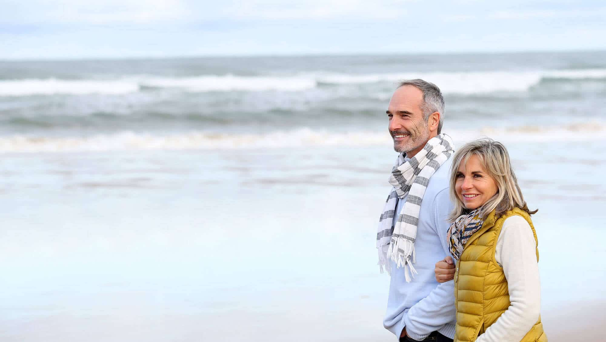 Senior couple walking on the beach in winter time | Cosmetic Laser Services in Seattle